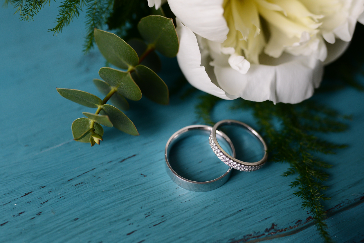wedding rings on turquoise table with peony flower